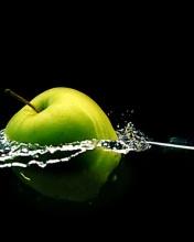 Сочное яблоко, падающее в воду на чёрном фоне непроницаемого бархата